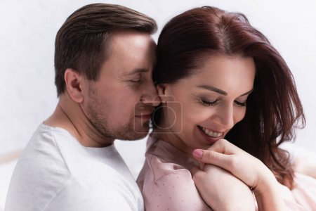 Man embracing cheerful wife with closed eyes at home