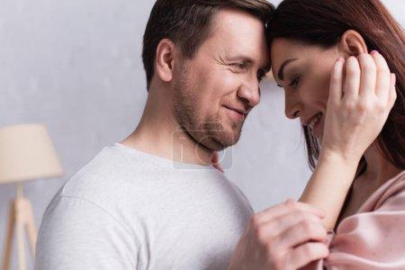 Homme adulte souriant tout en regardant sa femme à la maison