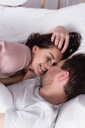 Smiling woman in pajama lying near husband on white bedding