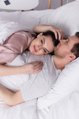 Adult woman lying on chest of husband on bed