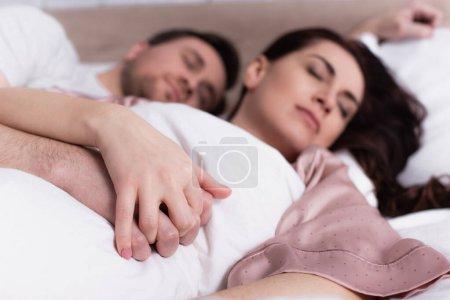 Photo pour Couple adulte tenant la main tout en dormant sur fond flou - image libre de droit