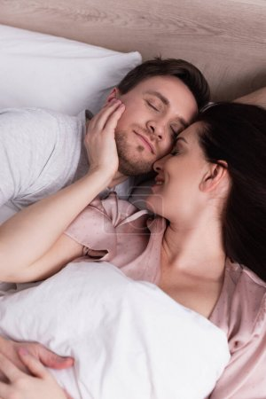Smiling woman touching face of sleeping husband on bed