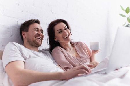 Photo pour Homme souriant utilisant un ordinateur portable sur le premier plan flou près de la femme avec tasse sur le lit - image libre de droit