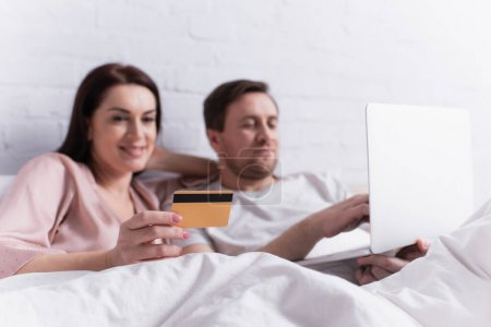 Credit card in hand of woman lying near husband with laptop on blurred background on bed