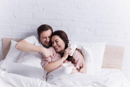 Homme chatouillant femme gaie avec smartphone et café près d'un ordinateur portable sur le lit