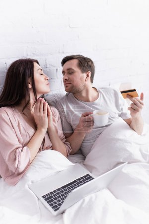 Photo for Adult couple with credit card, coffee and laptop sitting on bed - Royalty Free Image