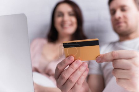 Credit card in hands of man near laptop and wife on blurred background