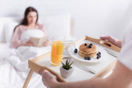 Mężczyzna trzyma śniadanie na tacy w pobliżu żony na niewyraźne tło w sypialni
