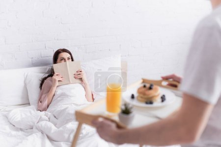 Photo for Woman holding book near husband with breakfast on blurred foreground in bedroom - Royalty Free Image