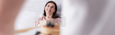 Smiling woman with book looking at blurred husband with pancakes in bedroom, banner