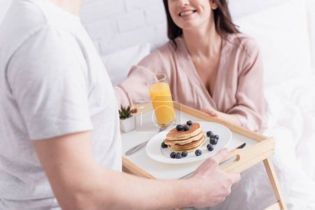 Cropped view of delicious pancakes and orange juice on tray near couple on blurred background in bedroom