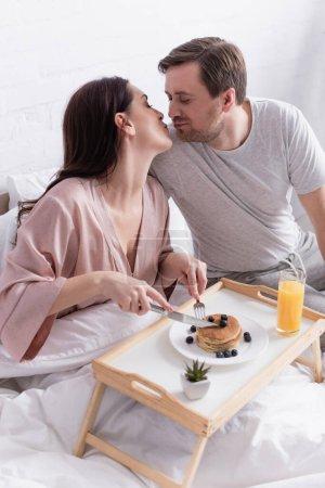 Photo pour Femme avec couverts coupant des crêpes et embrassant mari dans la chambre - image libre de droit