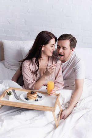 Photo pour Femme souriante nourrissant son mari près des crêpes et du jus d'orange au lit - image libre de droit