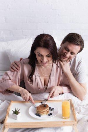 Photo pour Sourire homme étreignant femme coupe crêpe près de jus d'orange sur plateau sur le lit - image libre de droit