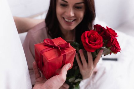 Photo for Man holding gift box near cheerful wife with flowers on blurred background on bed - Royalty Free Image