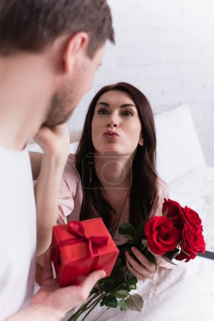 Woman with flowers pouting lips near husband with present on blurred foreground in bedroom