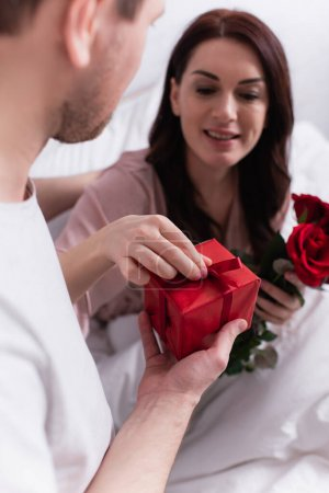 Man holding present near wife with roses blurred on bed