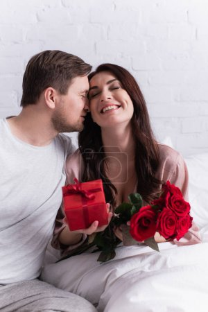 Man kissing happy wife with roses and flowers on blurred foreground in bedroom