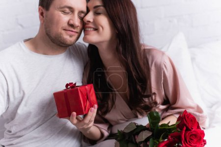 Smiling woman holding present and roses near husband in bedroom