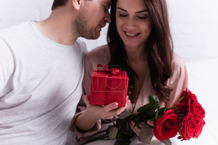 Photo for Gift and flowers in hands of happy woman near husband at home - Royalty Free Image