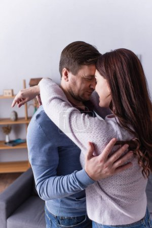 Man hugging brunette wife at home