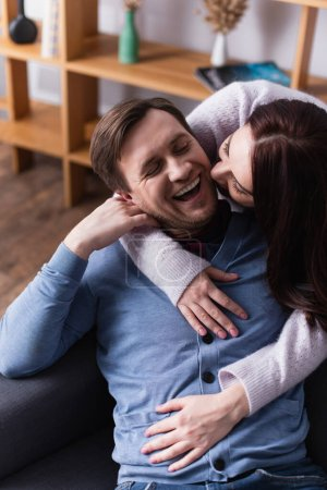 Brunette woman embracing cheerful husband on sofa at home