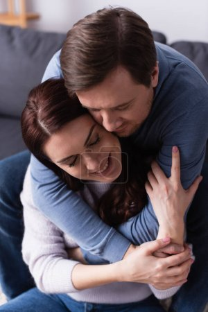 Photo for Man hugging happy brunette wife at home - Royalty Free Image