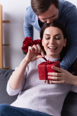 Smiling woman holding bow of gift box near husband with roses at home