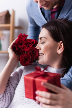 Photo for Smiling woman smelling roses while husband holding present on blurred foreground - Royalty Free Image