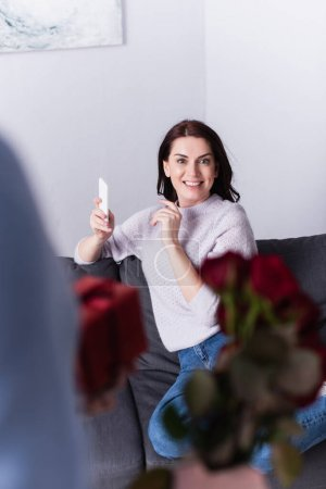Photo for Smiling woman holding cellphone near husband with flowers and present on blurred foreground - Royalty Free Image