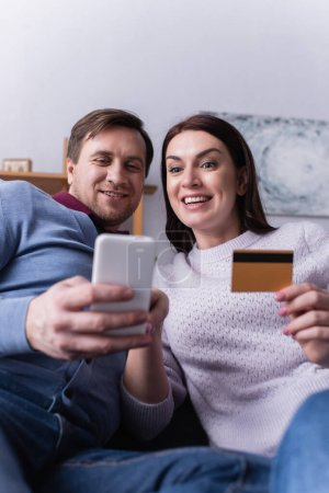 Photo for Adult couple using smartphone and credit card on blurred foreground - Royalty Free Image