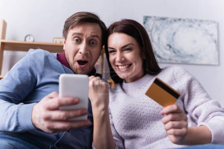 Photo for Excited couple with credit card using smartphone on blurred foreground - Royalty Free Image