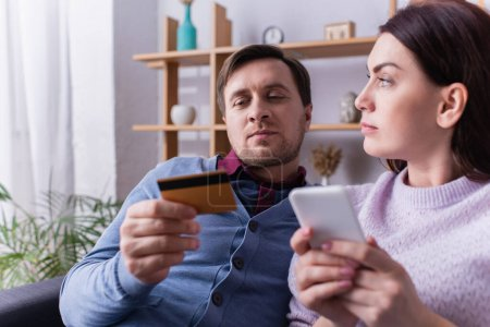 Photo for Man looking at credit card near wife with smartphone in living room - Royalty Free Image