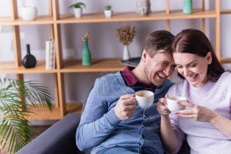 Smiling woman holding cup near husband on couch