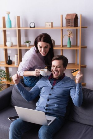 Excited man holding credit card near laptop and wife with cup at home