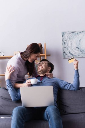 Photo for Cheerful couple with cup and credit card looking at each other near laptop - Royalty Free Image