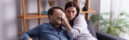 Photo pour Femme effrayée couvrant les yeux du mari sur le canapé, bannière - image libre de droit