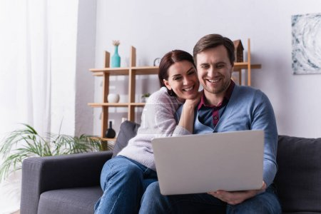 Happy adult couple using laptop on couch