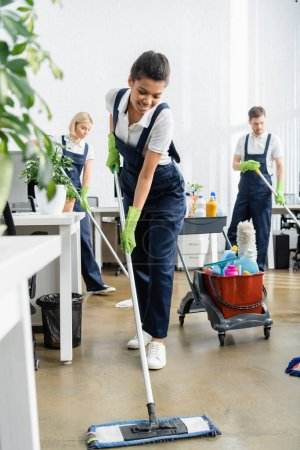 Photo for Positive african american cleaner washing floor near plant on blurred foreground in office - Royalty Free Image
