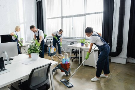 Multiethnic cleaners washing floor together in office