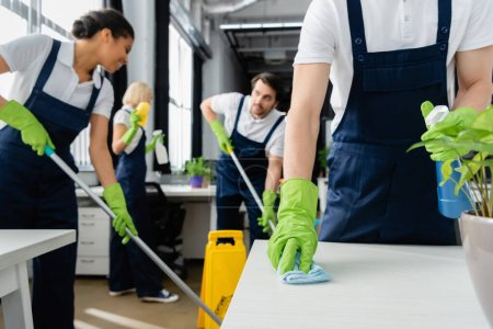 Cleaner cleaning table near plant and multiethnic colleagues on blurred background in office