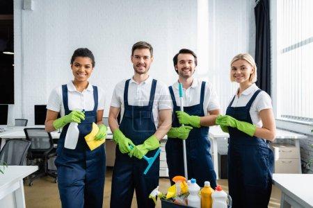 Photo pour Nettoyeurs interraciaux souriant à la caméra tout en tenant des fournitures de nettoyage dans le bureau - image libre de droit