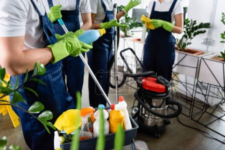 Photo for Cropped view of cleaner in rubber gloves holding detergent near colleagues and vacuum cleaner in office - Royalty Free Image