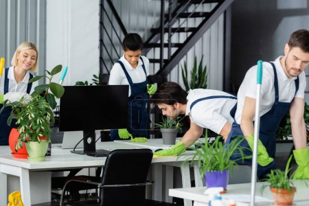 Multiethnic cleaners in uniform working near computer and plants in office