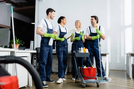Photo for Smiling multiethnic cleaners talking near cart with detergents in office - Royalty Free Image