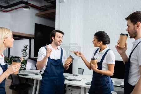 Photo for African american cleaner with coffee to go pointing at colleague in office - Royalty Free Image