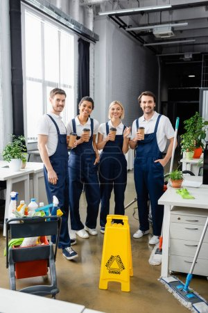 Cheerful multiethnic cleaners holding coffee to go near detergents in office