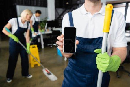 Photo pour Nettoyant tenant smartphone et balai dans le bureau - image libre de droit
