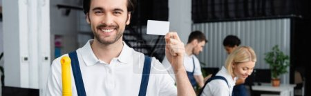 Smiling cleaner holding empty card near colleagues in office, banner