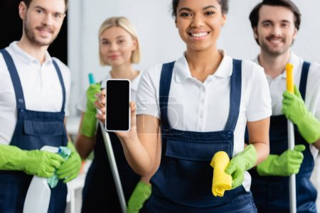 Smartphone in hand of african american cleaner smiling near colleagues on blurred background
